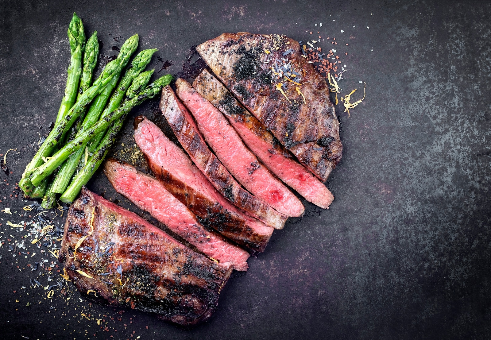 Barbecue dry aged wagyu flank steak sliced with green asparagus