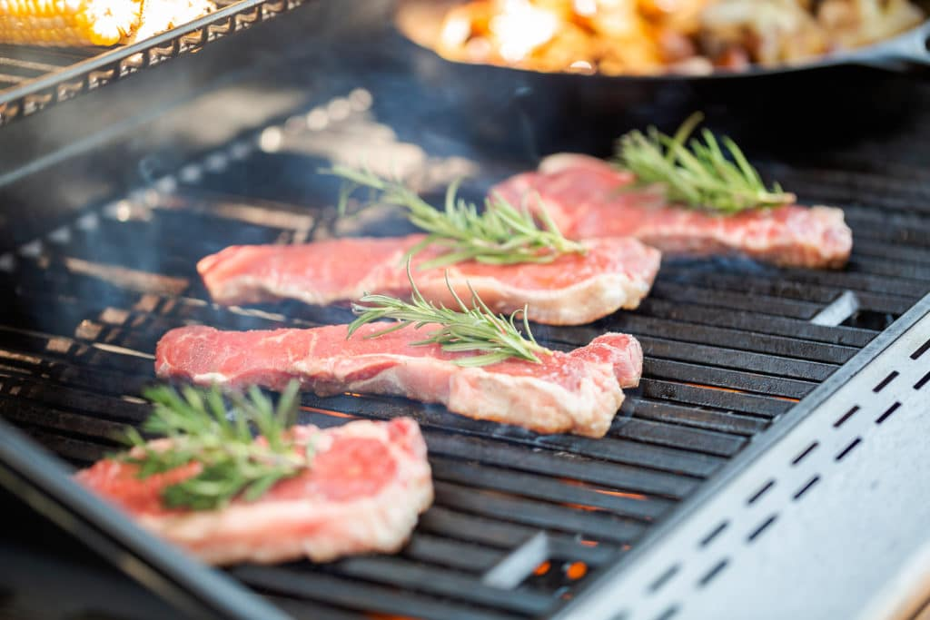 Grilling New York strip steak on outdoor gas grill.